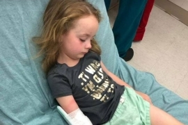 a little girl lying on a bed: Five-year-old Kailyn in the hospital following her brush with tick paralysis.