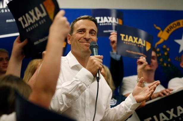 a person holding a sign: Republican state Attorney General Adam Laxalt won the GOP nomination on Tuesday to earn a spot on the ballot in November in Nevada's governor race.