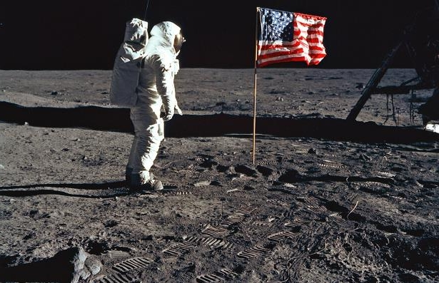 Astronaut Edwin E. Aldrin, Jr., the lunar module pilot of the first lunar landing mission, stands next to a United States flag July 20, 1969