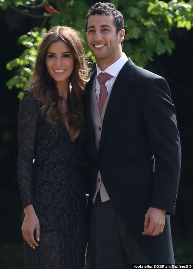 Daniel Ricciardo wearing a suit and tie standing next to a woman