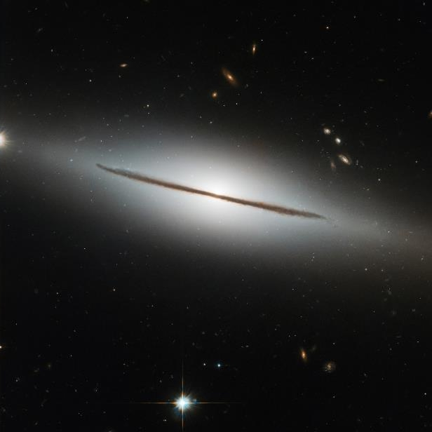 Slide 27 of 75: Resembling a wizard's staff set aglow, NGC 1032 cleaves the quiet darkness of space in two in this image from the NASA/ESA Hubble Space Telescope. NGC 1032 is located about a hundred million light-years away in the constellation Cetus (the Sea Monster). Although beautiful, this image perhaps does not do justice to the galaxy's true aesthetic appeal: NGC 1032 is actually a spectacular spiral galaxy, but from Earth, the galaxy's vast disk of gas, dust and stars is seen nearly edge-on.