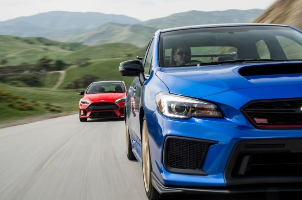 Slide 7 of 94: 2018-Subaru-WRX-STI-Type-RA-2018-Ford-Focus-RS-front-in-motion.jpg