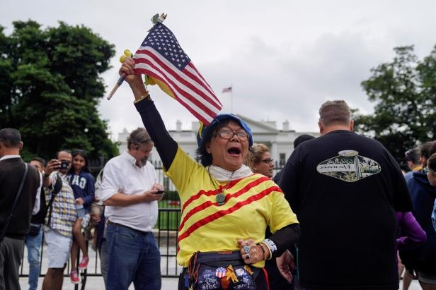 Victoria Kim, a Vietnamese Trump supporter, raises an American flag during a vigil on June 11, 2018, outside the White House to celebrate the Trump-Kim summit in Singapore.