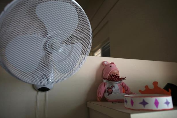 a close up of a fan: A doll and a paper crown are seen in the room of an elderly woman at the San Rafael nursing home in Arecibo