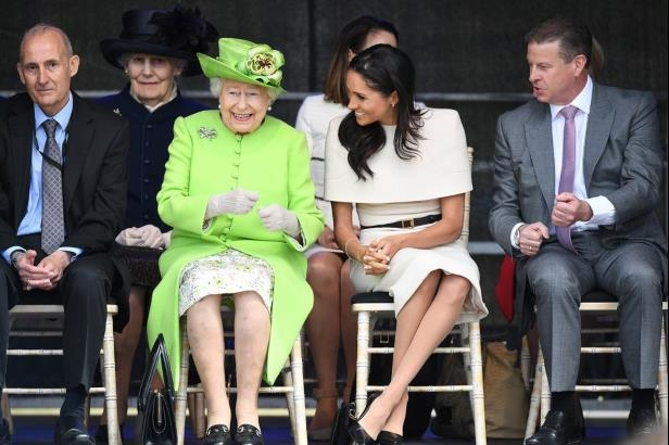 a group of people sitting on a bench: Meghan Markle and Queen Elizabeth
