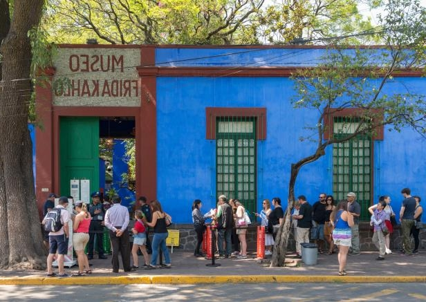 a group of people walking in front of a building: The Frida Kahlo Museum, a popular tourist destination, is in Coyoacán, in the southern part of the city.