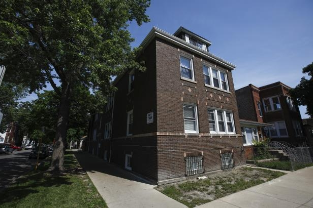 a large brick building with grass in front of a house: The building at 5701 W. Belden Avenue in Chicago where feds say a husband and wife ran a high-end prostitution ring involving young Indian actresses brought to the U.S. on promises to help their careers. Thursday, June 7, 2018.