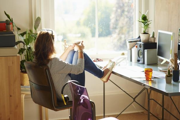Image: Pensive woman looking through window with feet up on desk in sunny home officeSunlight is the easiest way for the body to absorb vitamin D, but too much UV exposure can increase risk of skin cancer.