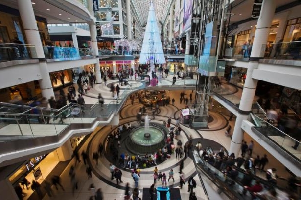 People go shopping in the Eaton Centre shopping mall as they walk by a giant Christmas Tree in Toronto.