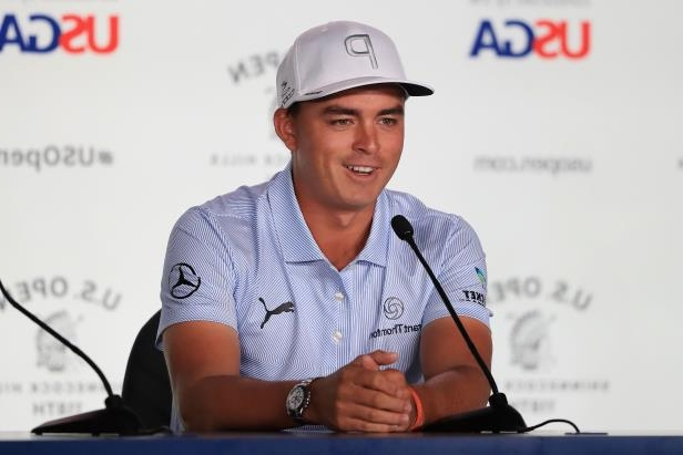 Rickie Fowler wearing a hat and smiling at the camera