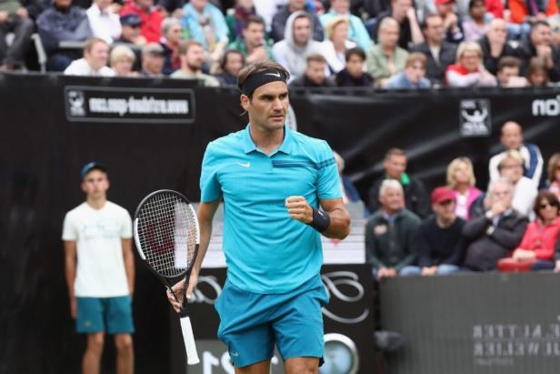 Roger Federer standing in front of a crowd holding a racket on a court: Alex Grimm/Getty Images Sport