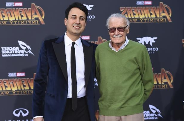 Stan Lee holding a sign posing for the camera: Stan Lee, left, and Keya Morgan arrive at the world premiere of