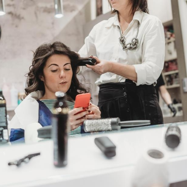 a man and a woman standing in front of a mirror: How to Break Up With Your Hairstylist - the Right Way