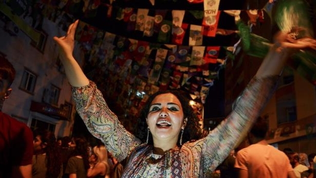 Women dance under election banners of the HDP in the mainly-Kurdish city of Diyarbakir: Kurds in Diyarbakir celebrated the HDP's result