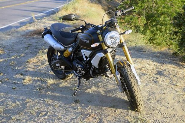 a motorcycle parked on the side of a dirt road: 2018 Ducati Scrambler 1100 Sport