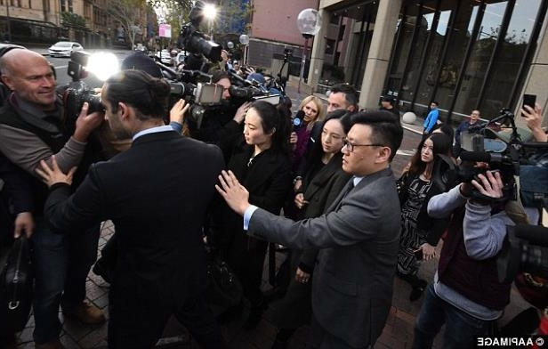 a group of people standing in front of a crowd: The judge expressed her fear of Gao fleeing the country because of the lack of an extradition treaty between China and Australia