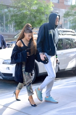 a man and a woman standing on a sidewalk: Ariana Grande Pete Davidson
