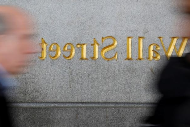 FILE PHOTO: People walk by a Wall Street sign close to the NYSE in New York