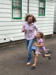 a little girl standing in front of a building: Dawn Johnson playing a running game with Stella in their shared driveway