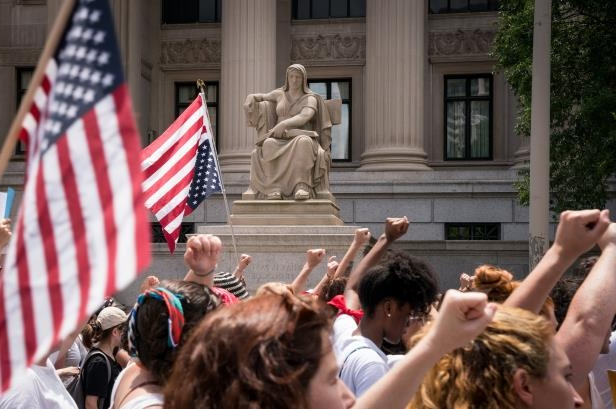 a group of people jumping in front of a crowd: Women marched to the Capitol in Washington on Thursday to protest the detention of undocumented migrant families.