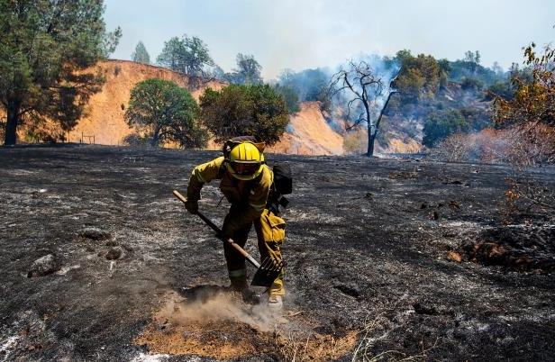 a man riding a bike down a dirt road: Jack Miguel of the Keyes Fire Department attacks a hot spot during the County Fire on Sunday, July 1, 2018 in Capay Valley, Calif. The fire has grown to 44,500 acres as of 7:30 a.m. Monday, up from a reported size of 32,500 acres Sunday night, according to Cal Fire.