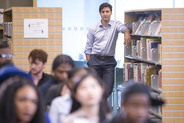 Prime Minister Justin Trudeau listens to his introduction before a town hall Q&A with youth at a hiring fair held in a Toronto Library, on Wednesday.