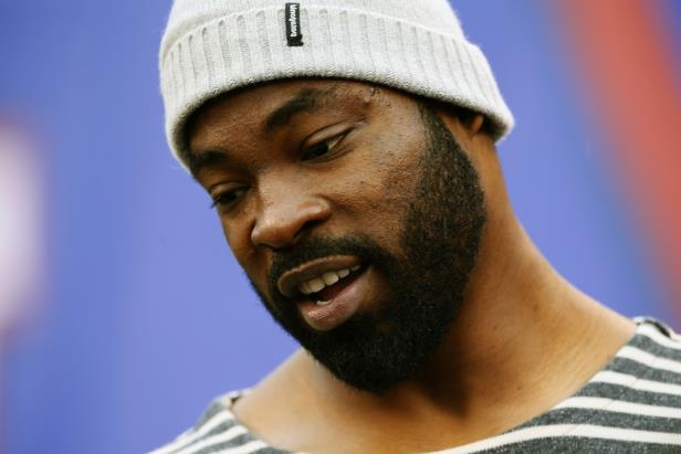 a close up of Justin Tuck wearing a hat