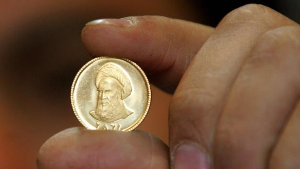 File photo showing an Iranian gold trader holding a gold coin in Tehran (19 April 2006): The value of gold coins has risen sharply in Iran in recent weeks