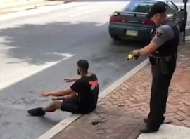 a group of people on a sidewalk: Suspect, Sean Williams, 27, is told to sit down on the sidewalk but the cop still has his taser out