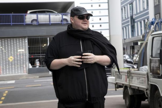 a man riding on the back of a truck: German tech entrepreneur Kim Dotcom arrives for a court hearing in Auckland, New Zealand