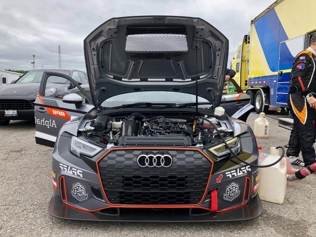 a car parked in front of a truck: Audi RS3 LMS TCR