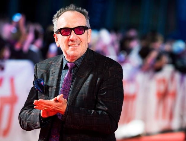 a man wearing a suit and tie talking on a cell phone: Elvis Costello poses for photographs on the red carpet during the 2017 Toronto International Film Festival.