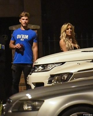 a man and a woman standing in front of a car: Glamorous: She styled her newly blonde locks into a blow-dried curly tousled hairdo as she added a slick of glamorous make-up