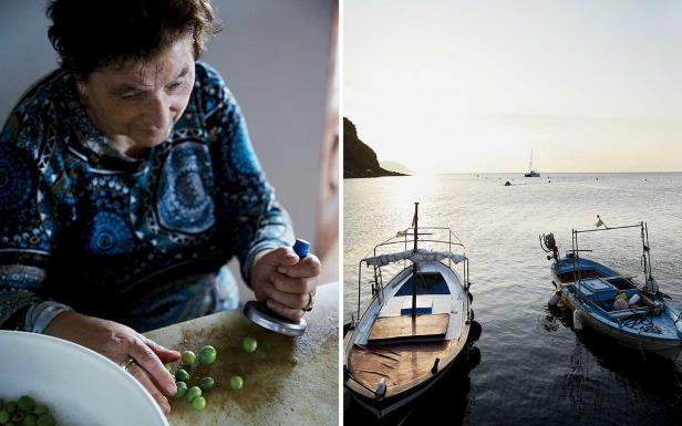 a person sitting on a boat in the water: Fron left: The harbor of the village of Pecorini Mare, on Filicudi; preparing olives at the restaurant Villa La Rosa, on Filicudi.