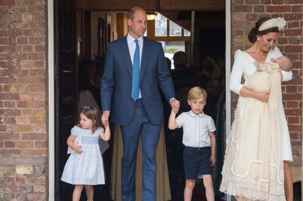 a group of people standing in front of a brick building: The Duke and Duchess of Cambridge with their children Prince George, Princess Charlotte and Prince Louis