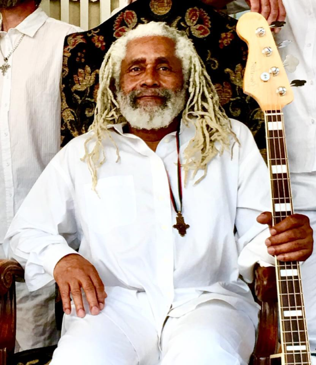 a man holding a guitar: Big Sugar bassist Gary Lowe died after battle with cancer on Saturday. He was 65.