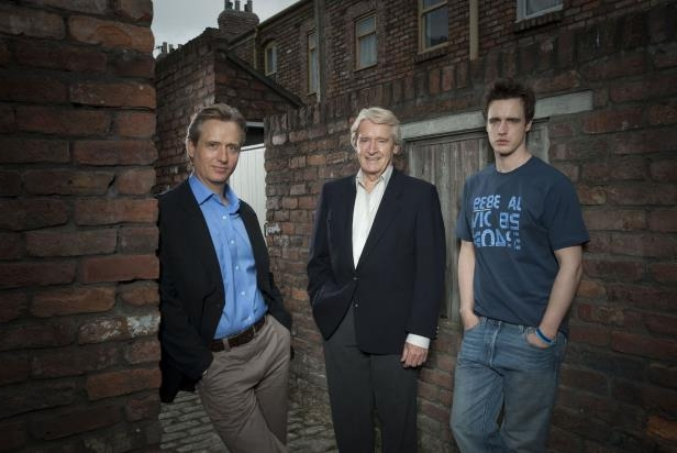 a man standing in front of a brick building: James Roache, Bill Roache and Linus Roache in Coronation Street in 2010