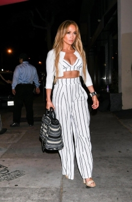 a woman standing on a sidewalk: Jennifer Lopez
