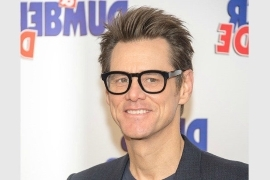 Jim Carrey wearing glasses and smiling at the camera