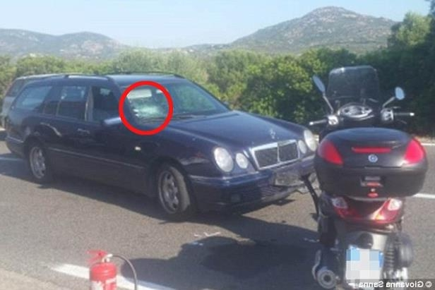 a car parked on the side of a road: Crash: George Clooney has reportedly been hospitalised following a bike accident in Puntaldìa, Sardinia, on Tuesday morning - (pictured) when he hit a car's windscreen