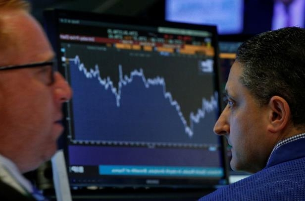a man sitting in front of a computer screen: Traders work on the floor of the New York Stock Exchange in New York in this July 6 photo. Stocks were up across North America on Monday following positive economic data from Canada and the U.S. last week, market watchers said.