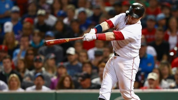 a man swinging a baseball bat in front of a crowd: Christian Vazquez