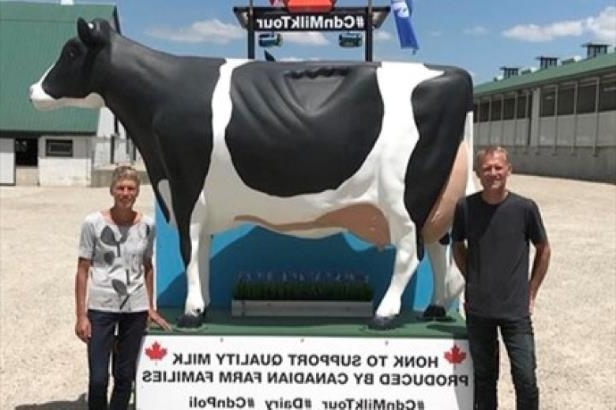 a person standing next to a cow: Henk and Bettina Schuurmans pose on their cross Canada tour.