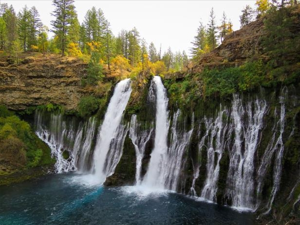 a large waterfall over some water with McArthur–Burney Falls Memorial State Park in the background: Conditions are near peak at Burney Falls in McArthur-Burney Falls Memorial State Park in the Shasta Cascade.