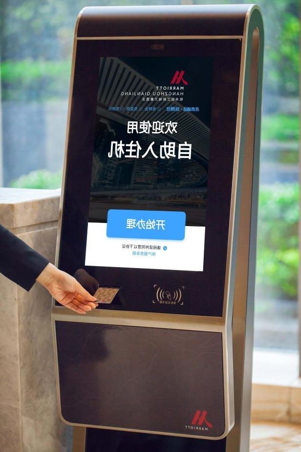 a sign in front of a window: A look at Marriott's new facial recognition kiosk.