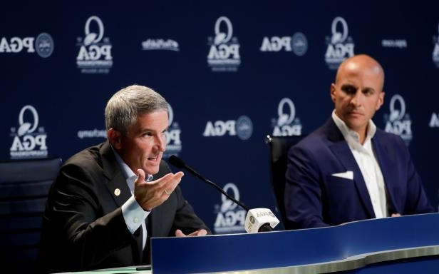 FILE - In this Aug. 8, 2017 file photo PGA Tour commissioner Jay Monahan speaks as Peter Bevacqua, CEO of the PGA of America, listens during a news conference at the PGA Championship golf tournament at the Quail Hollow Club in Charlotte, N.C., to announce the PGA Championship moving to May. Cooperation between the two groups was pivotal in the PGA Tour revamping its schedule. (AP Photo/Chris Carlson)