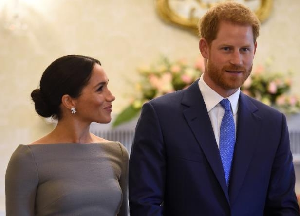 Prince Harry wearing a suit and tie: Britain's Prince Harry and his wife Meghan, Duchess of Sussex, smile as they prepare to meet Ireland's President, Michael Higgins, on their second day of a two-day visit to Dublin