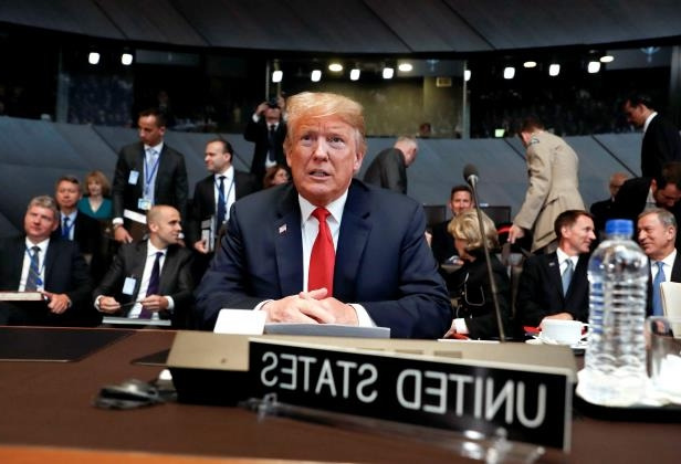 Slide 1 of 9: U.S. President Donald Trump takes his seat as he attends the multilateral meeting of the North Atlantic Council in Brussels, Belgium July 11.