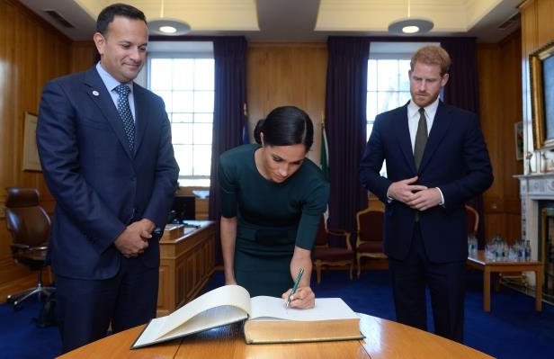 Slide 12 of 14: Britain's Prince Harry and his wife Meghan, the Duke and Duchess of Sussex, sign the visitors book in the office of the Taoiseach Leo Varadkar, at the start of a two-day visit to Dublin, Ireland July 10, 2018.  REUTERS/Clodagh Kilcoyne