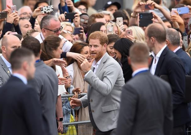 Slide 3 of 86: Britain's Prince Harry signals to a member of the public during a walkabout in Parliament Square in Trinity College, Dublin, Ireland, July 11, 2018. REUTERS/Clodagh Kilcoyne